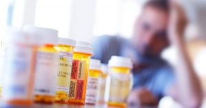 A large group of prescription medication bottles sit on a table in front of a distraught man who is leaning on his hand as he sits at his dining room table