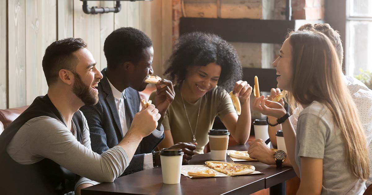 Group of young people laughing eating pizza together in pizzeria