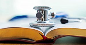 A stethoscope is placed on top of an open book