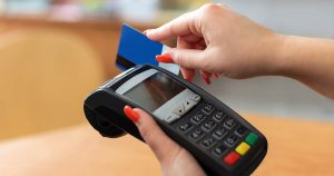 A woman is swiping her credit card