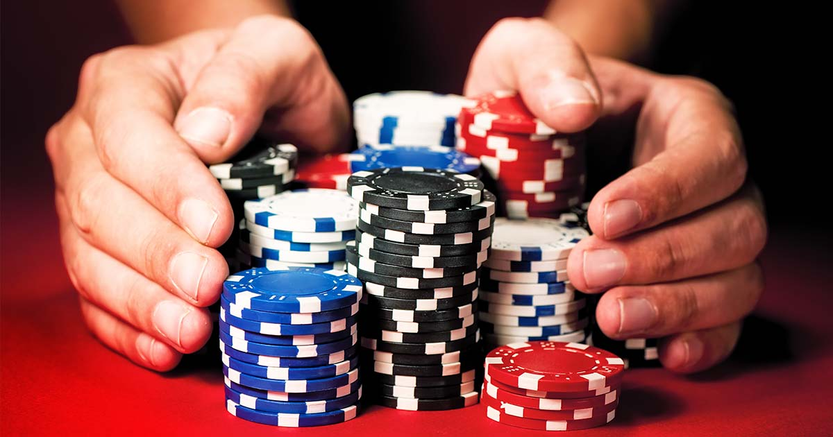 A person is pushing all their casino chips forward
