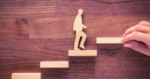 Wooden figure walking up stairs