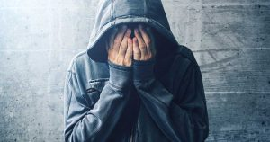 Man is wearing a hoodie and is covering his face with his hands