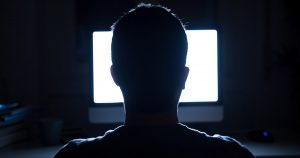 Man sitting in front of his computer in the dark